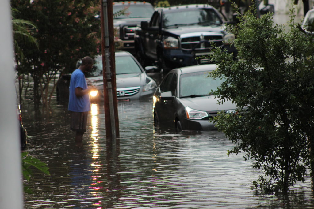 New Orleans flash flood waters rise around curb-parked cars in neighborhoods.