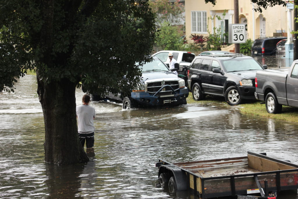 Neighbors camp out to warn cars to slow down in deep waters.