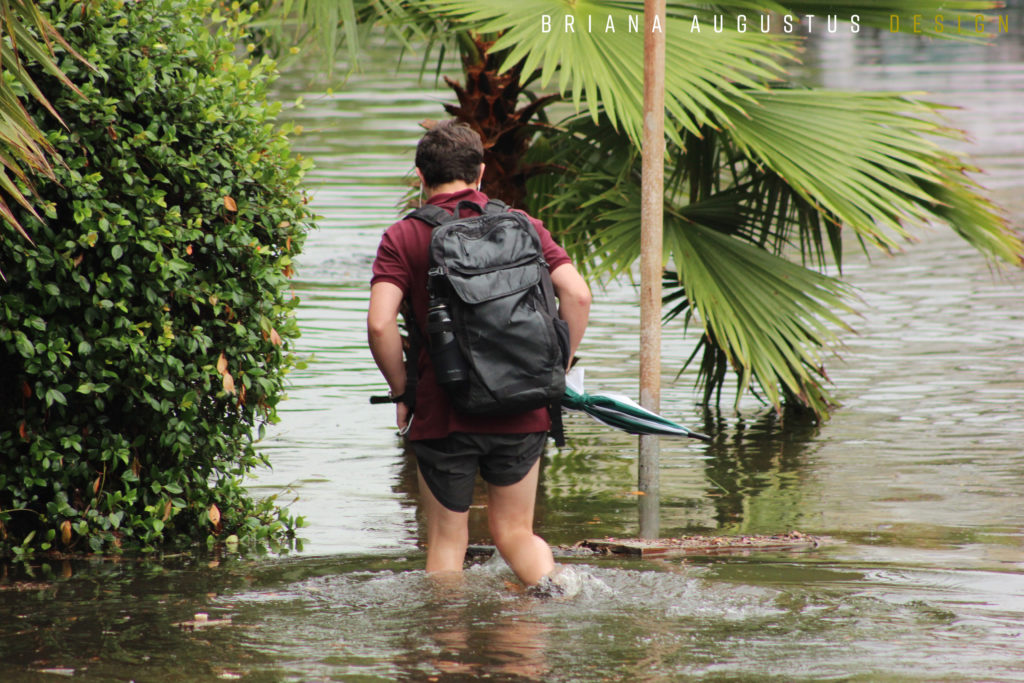 Man wading through flooded street.