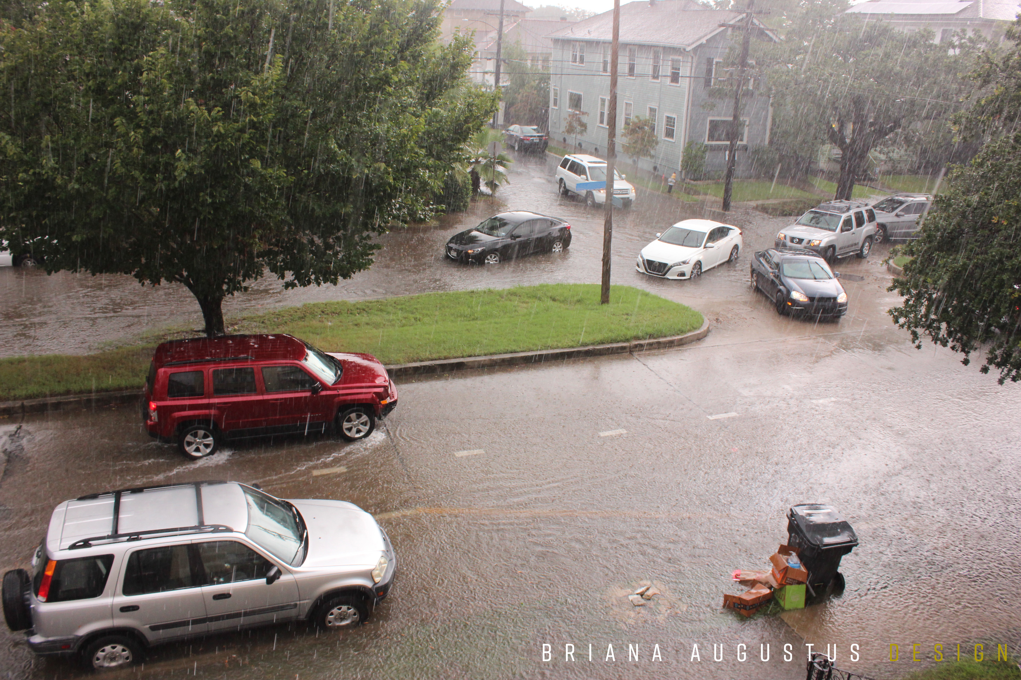 Cars reversing mid-intersection during early Monday evening traffic due to flooded roadway.