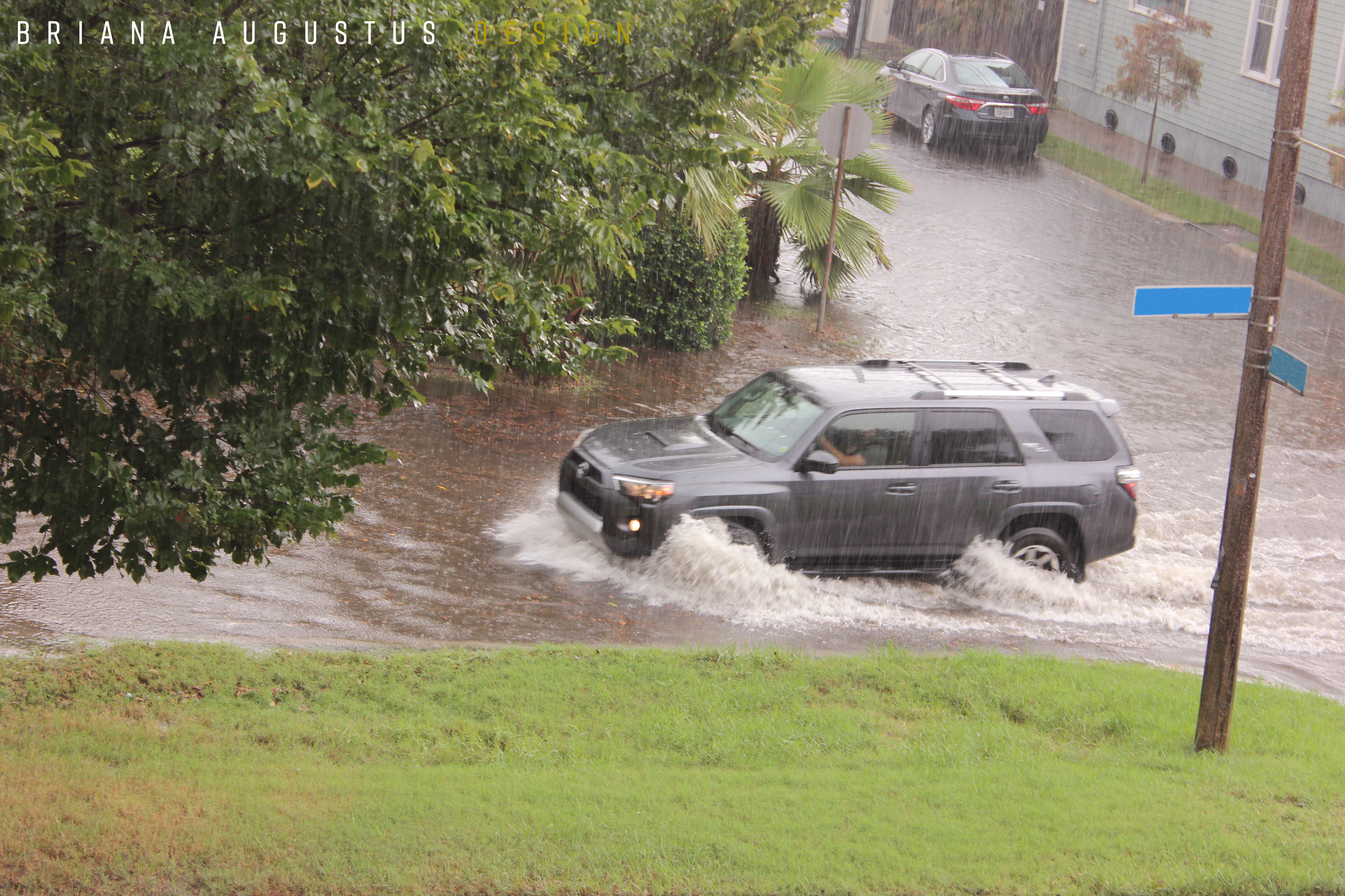SUV wading through flooded roadway.